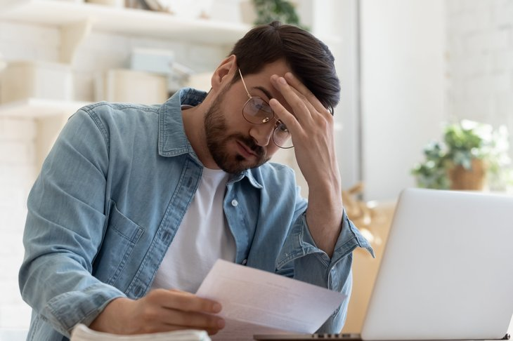 upset man reading a letter from the IRS
