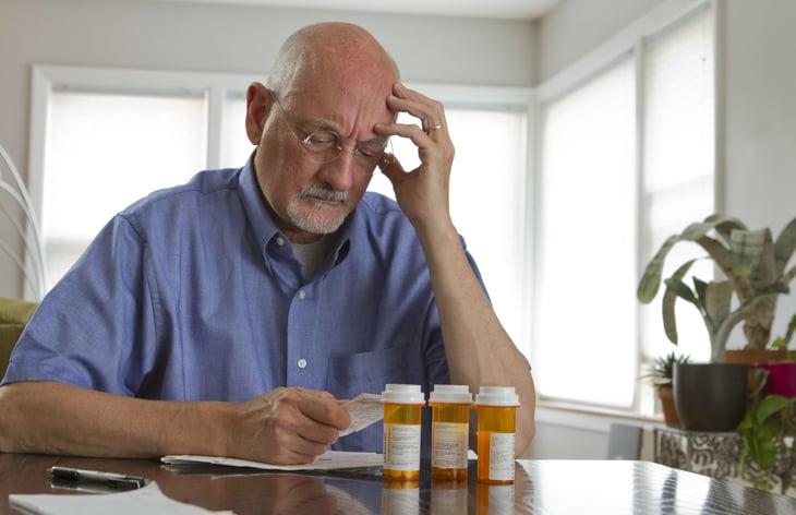 An older man stresses over prescription drugs