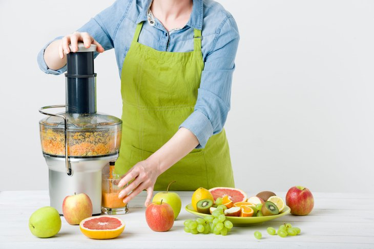 Woman making fruit juice with a juicer