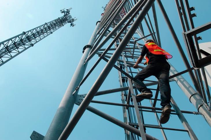 Telecommunications maintenance worker climbing a tower