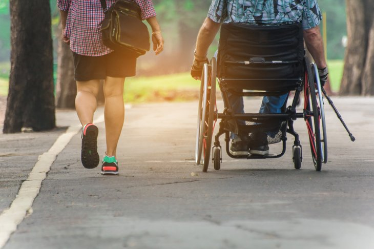 Couple in a park, one walking, one in a wheelchair