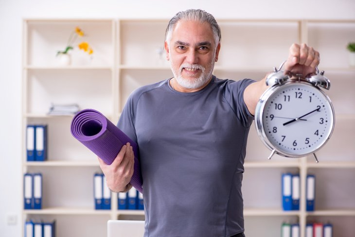 Royalty-free stock photo ID: 1341148454 White bearded old man employee doing exercises in the office