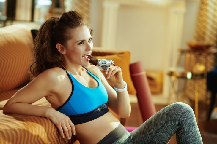 A woman in workout clothing eats a chocolate protein bar