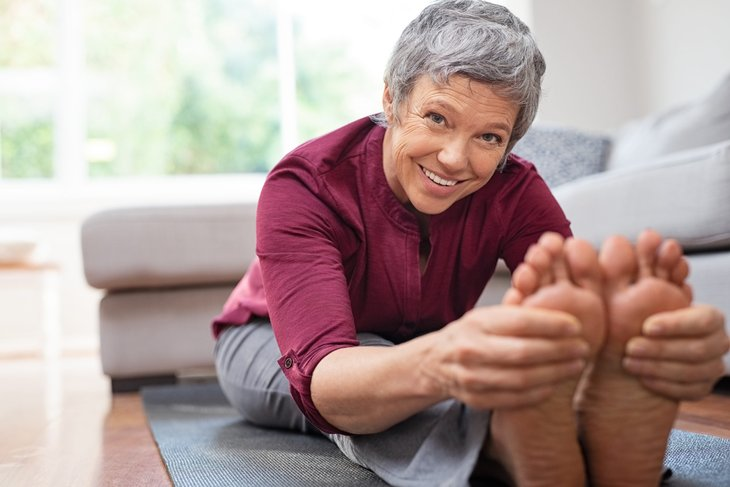 A senior stretches her legs while on a yoga mat during a workout at home