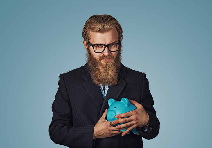 A greedy businessman in glasses clings to his piggy bank