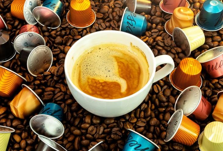 Nestle Nespresso pods surround a cup of espresso coffee