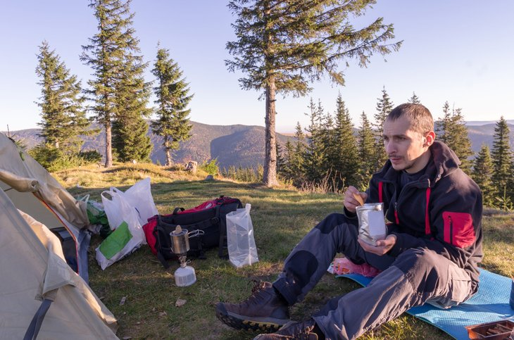 A backpacker eats freeze-dried food while camping