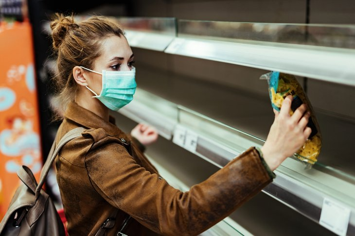 A woman in a surgical mask shops at a grocery store with empty shelves