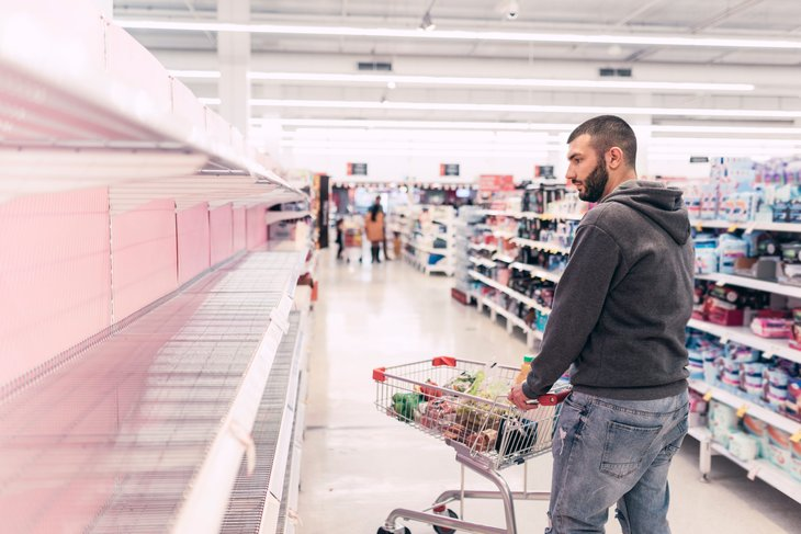 A shopper pushes a cart through a store with empty shelves