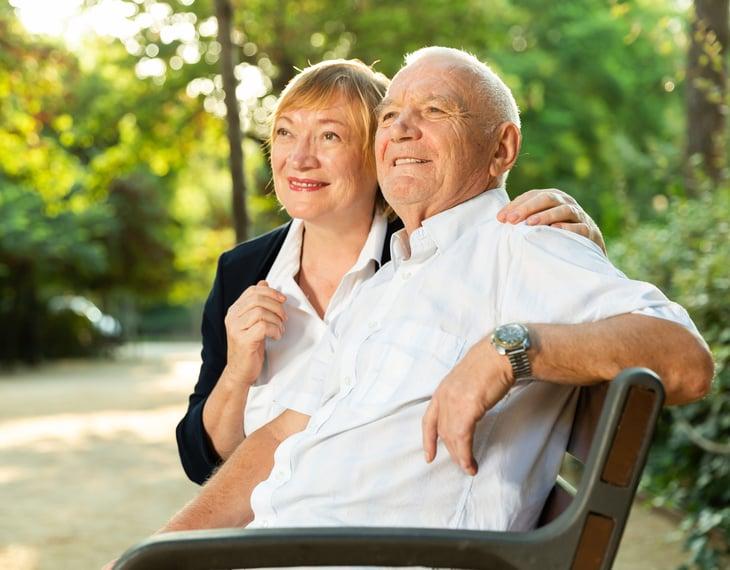 A senior couple enjoys the outdoors on a bench in a park