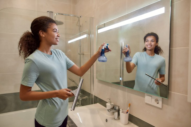 A young woman cleans her bathroom mirror with a spray bottle and squeegee