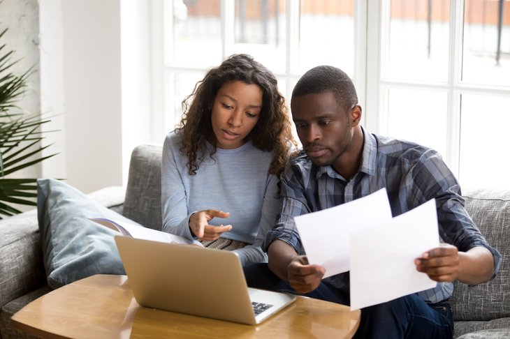A young couple review financial documents over a laptop computer in their living room