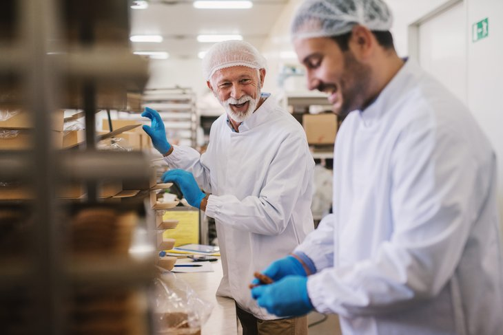 Royalty-free stock photo ID: 1195311625 Picture of two male food factory employees in sterile clothes packing fresh made cookies and having fun.
