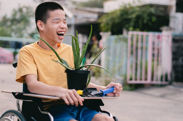 Child in a wheelchair holding an aloe vera plant