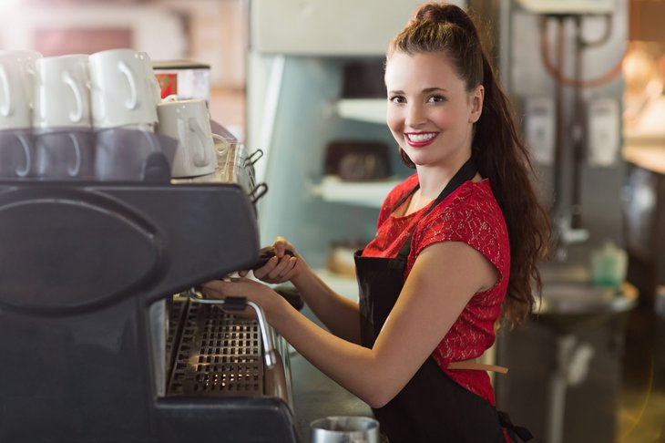 A 15-year-old girl working at a coffee shop prepares morning brew for customers