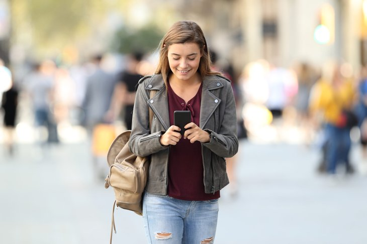 A young woman smiles because she's paid to walk with her phone using apps like StepBet and GigWalk