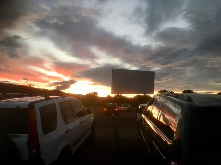 Cars parked at a drive-in-theater during sunset