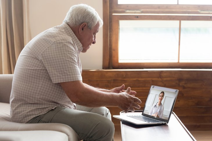 An elderly man speaks to his doctor remotely on his laptop