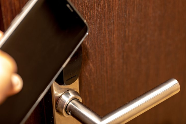 Someone unlocking their hotel room door with a smartphone