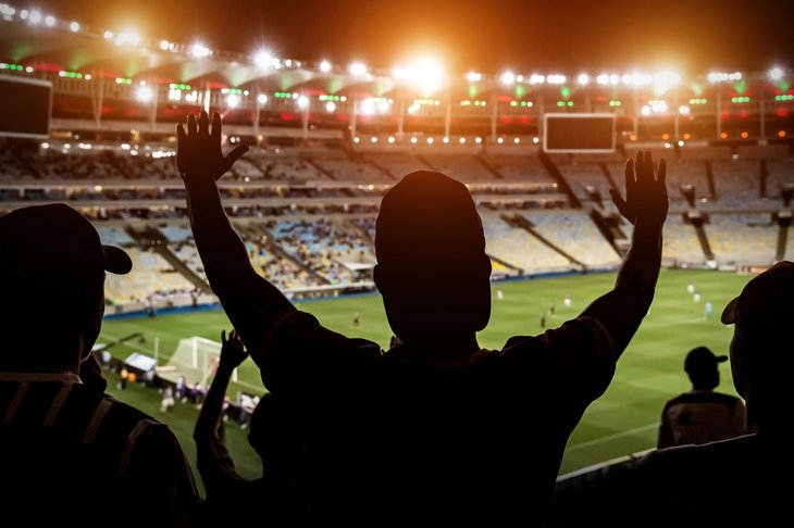 A man celebrating a goal at the soccer match in a stadium at night