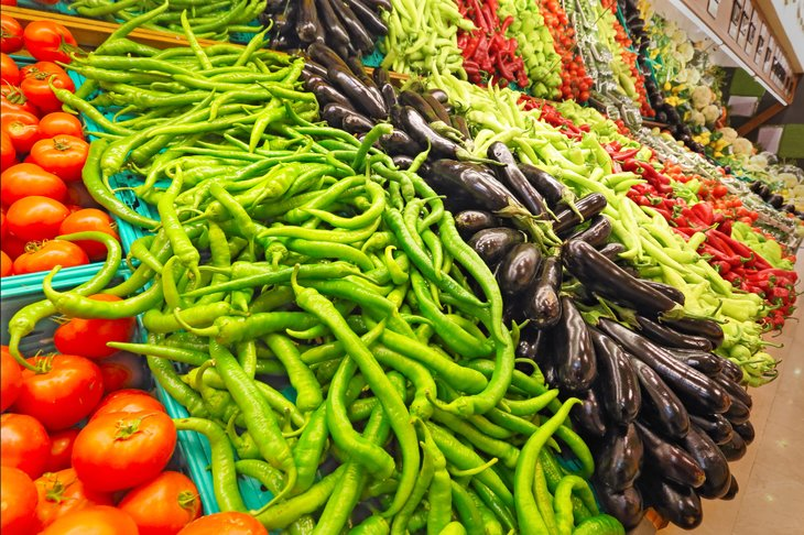 A variety of colorful vegetables at the market, including tomatoes, peppers and eggplant