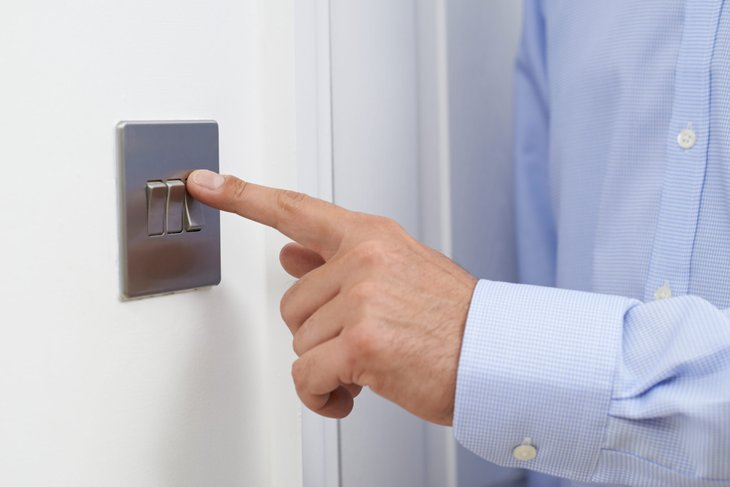 A man flips a light switch