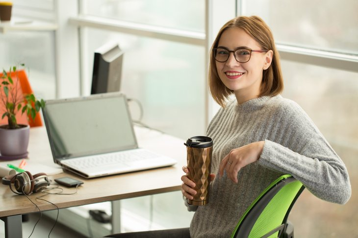 woman holding a reusable thermos