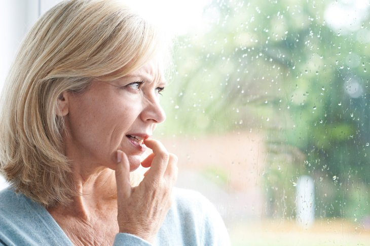 Worried older woman looking at a window as it rains