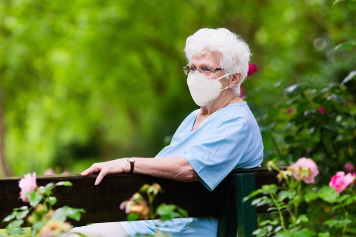 An older woman wears a face mask in the park during the coronavirus