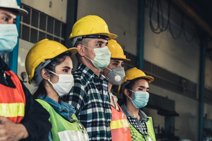 A group of construction workers in face masks are unemployed because of COVID-19