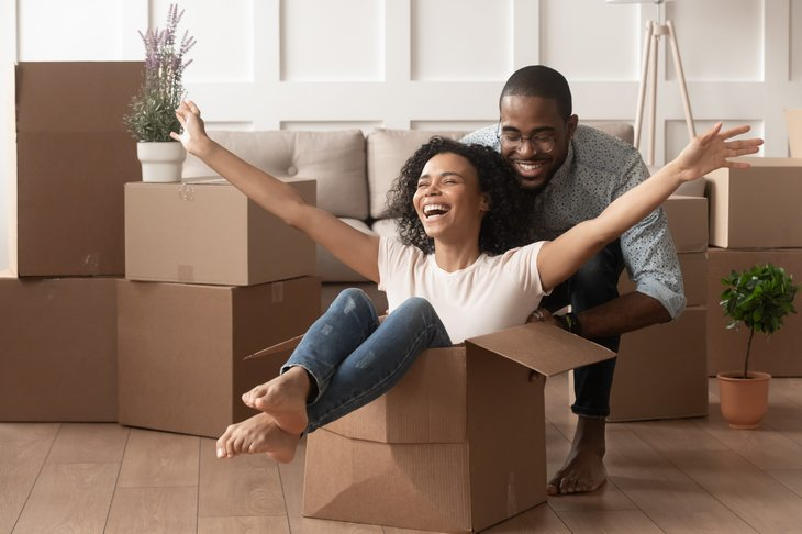 A millennial Black couple happily packs to move to another city