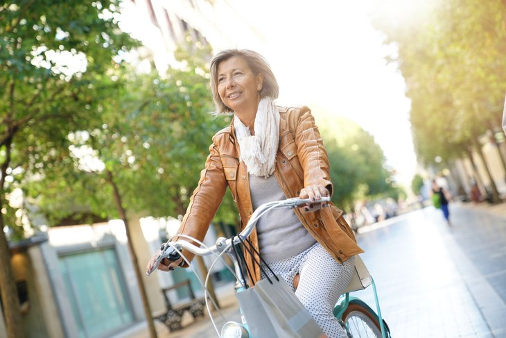 A happy woman riding a bike in a city