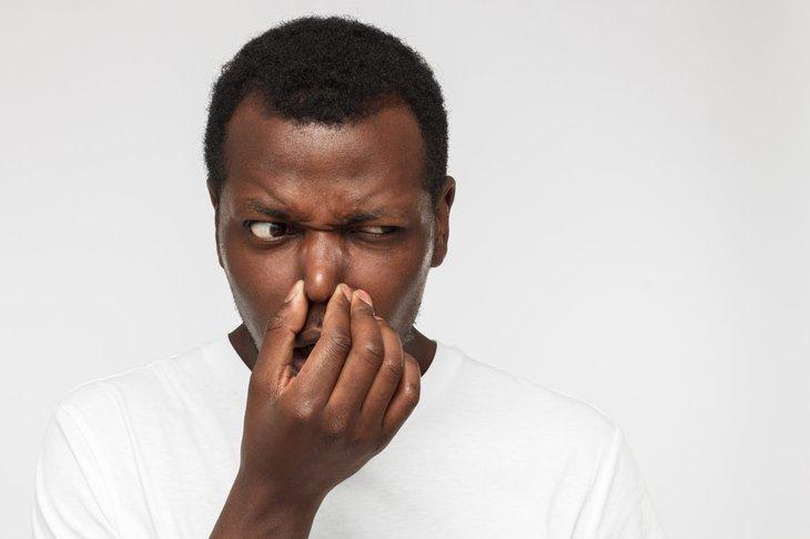 Man smelling bad odor