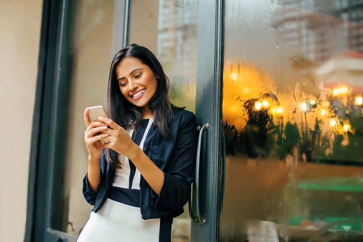 A young woman happy with her new cellphone plan texting outdoors