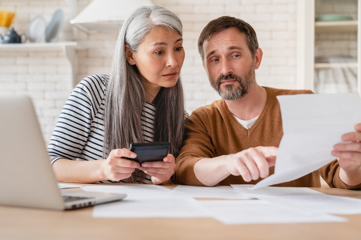 Couple reviewing financial documents in their kitchen