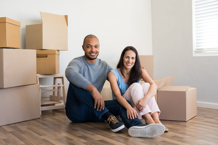A happy couple with boxes sitting on the floor of their new home