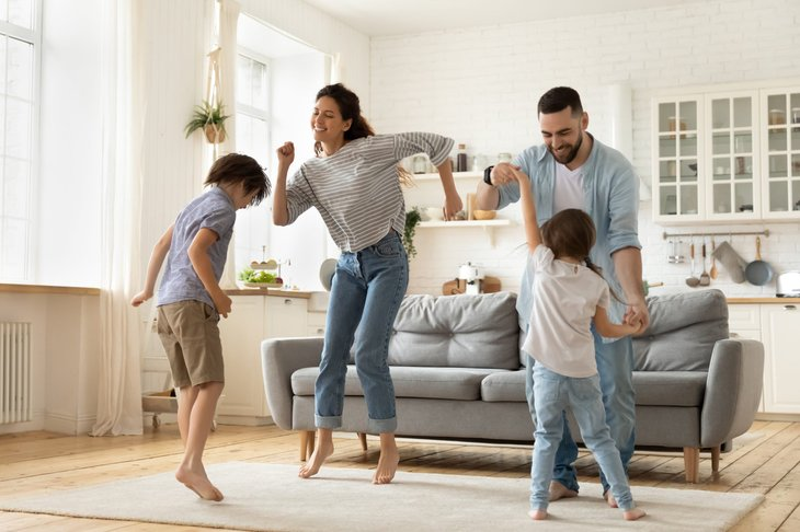 A happy family of parents and two children dancing in the living room