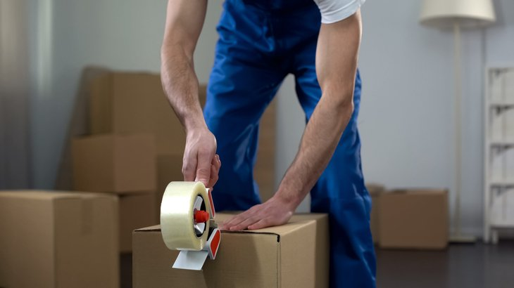 Man packing up a box for moving