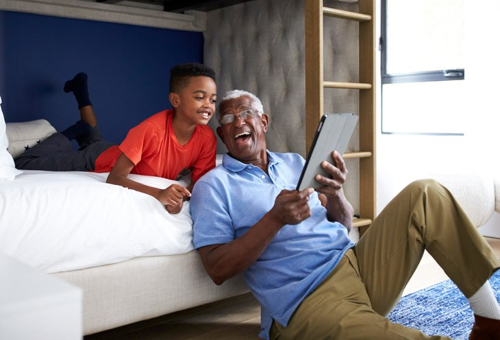 Grandfather using a tablet with his grandchild