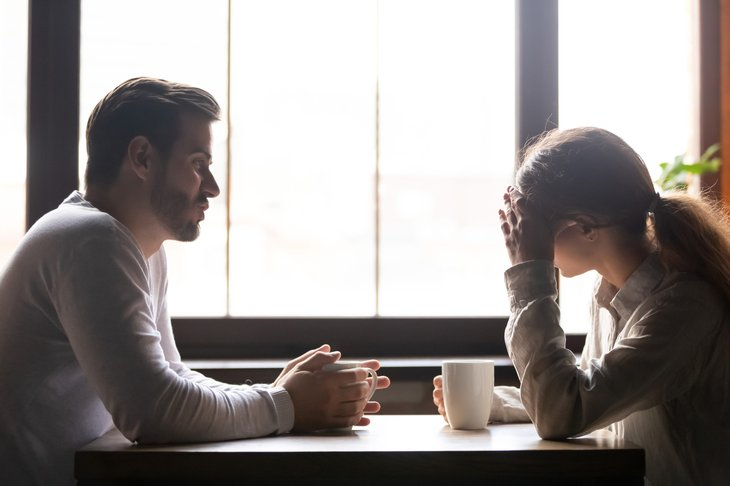 A stressed couple discusses family finances at the dinner table
