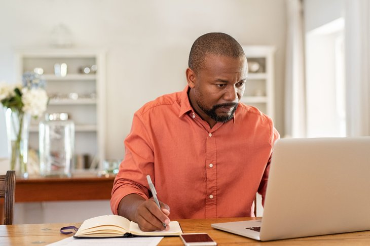 A Black man plans his finances on his laptop and with notes