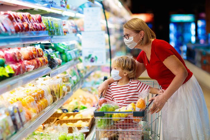 Mother and child grocery shopping in masks