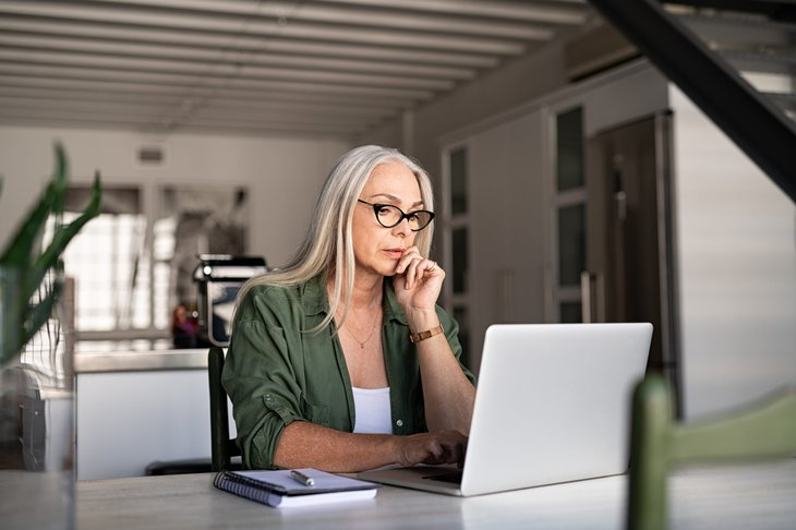 Older woman working on laptop and stressed