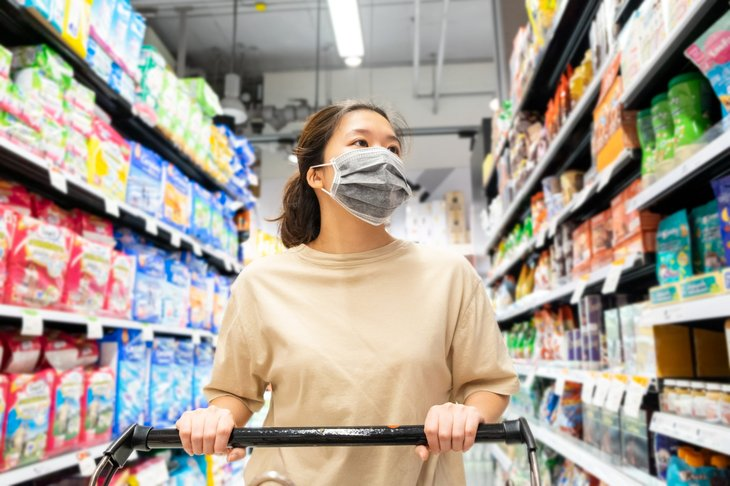 Woman in a mask shopping for groceries