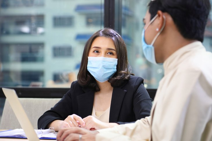 Businesswoman and man wearing masks in a meeting
