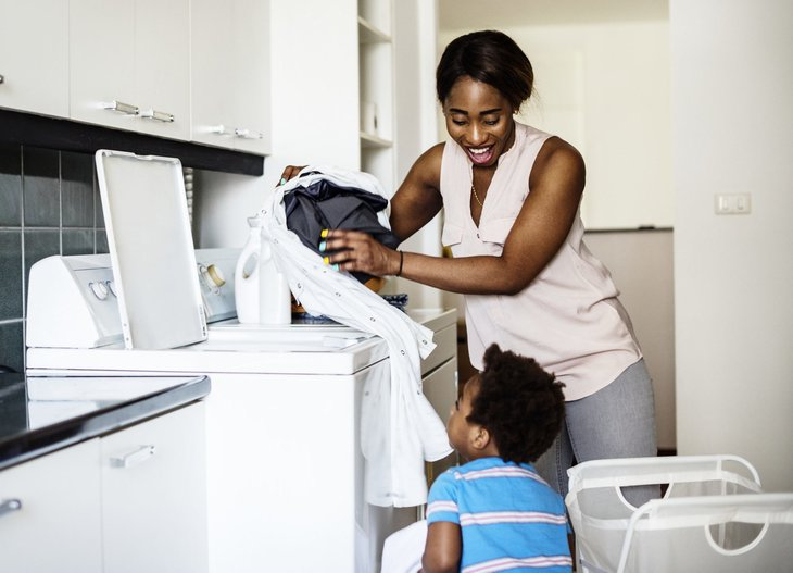 Mother doing laundry with her child