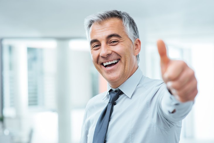 An older businessman gestures thumbs up