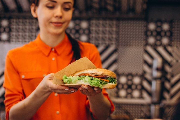 Woman holding a sub sandwich