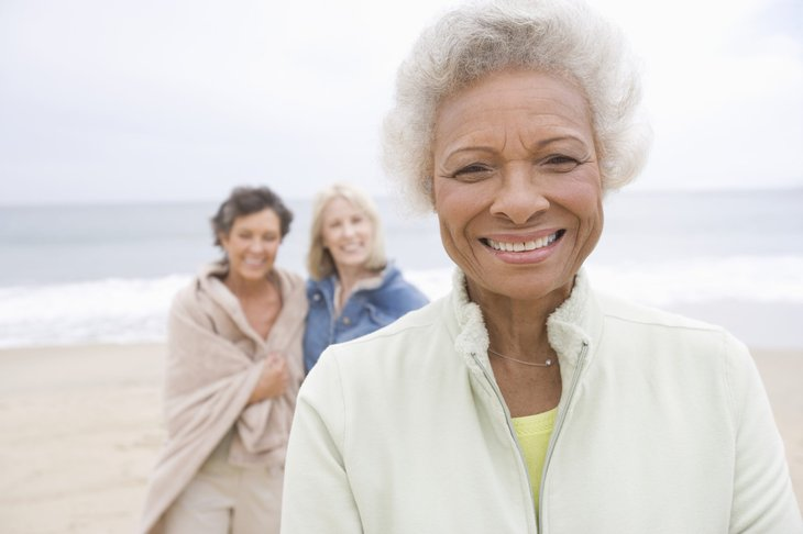 Senior woman on the beach with friends