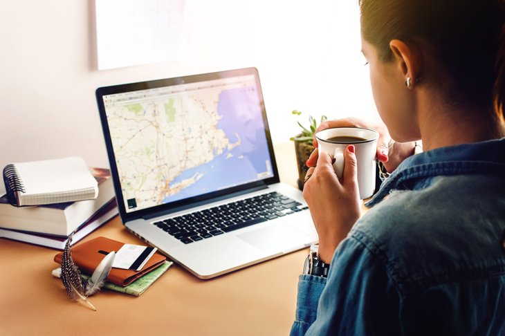 Woman studying a map on her laptop
